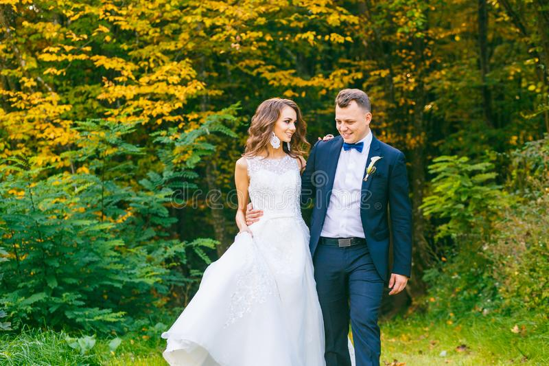 Elegante gelockte Braut und stilvoller Bräutigam lizenzfreie stockfotos