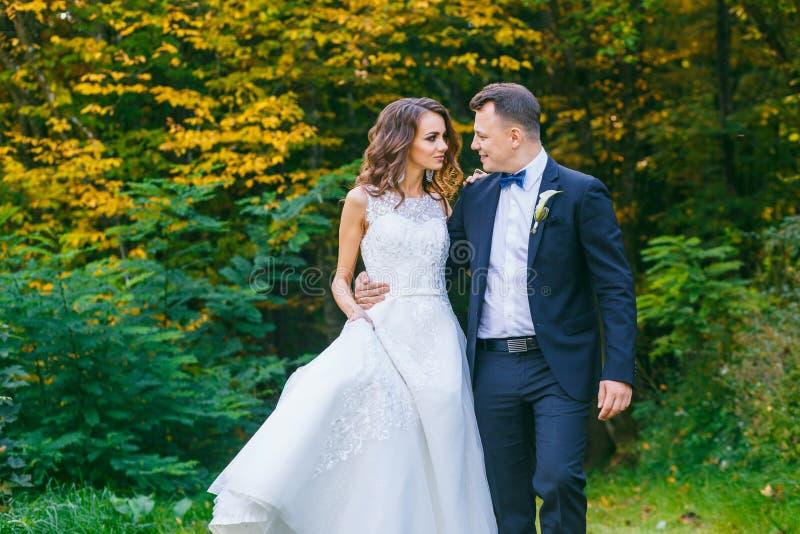 Elegante gelockte Braut und stilvoller Bräutigam stockbilder