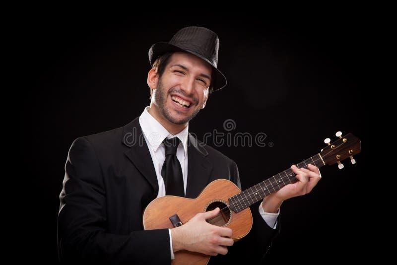 Elegante gelukkige die de musicus van de mensenzanger het spelen ukelelegitaar op zwarte wordt geïsoleerd stock afbeeldingen