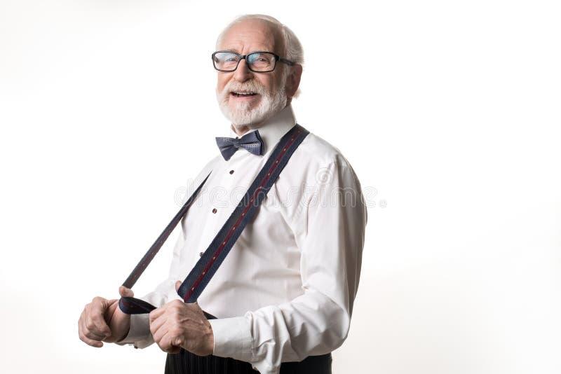 Elegante gepensioneerde die zijn nieuwe bretels tonen royalty-vrije stock foto's