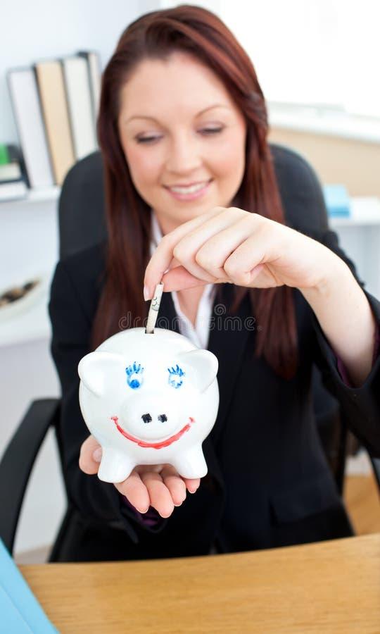Elegante Geschäftsfrau, die Geld in ein piggybank einsetzt lizenzfreies stockbild