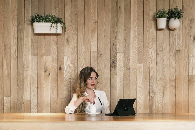 Elegante Geschäftsfrau, die mit einer Tablette in einem Restaurant arbeitet lizenzfreie stockbilder