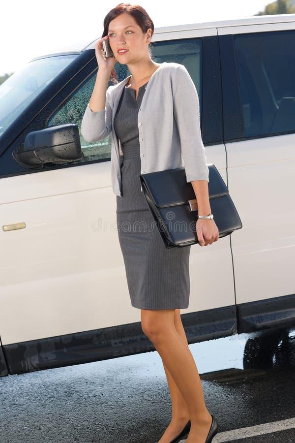 Elegante Geschäftsfrau stehen das Luxuxauto Benennen bereit stockbilder