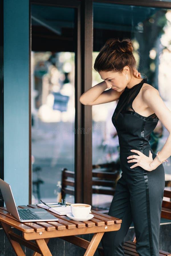 Elegante Geschäftsfraustellung nahe einer Tabelle in einem Caféweileblick stockfotografie