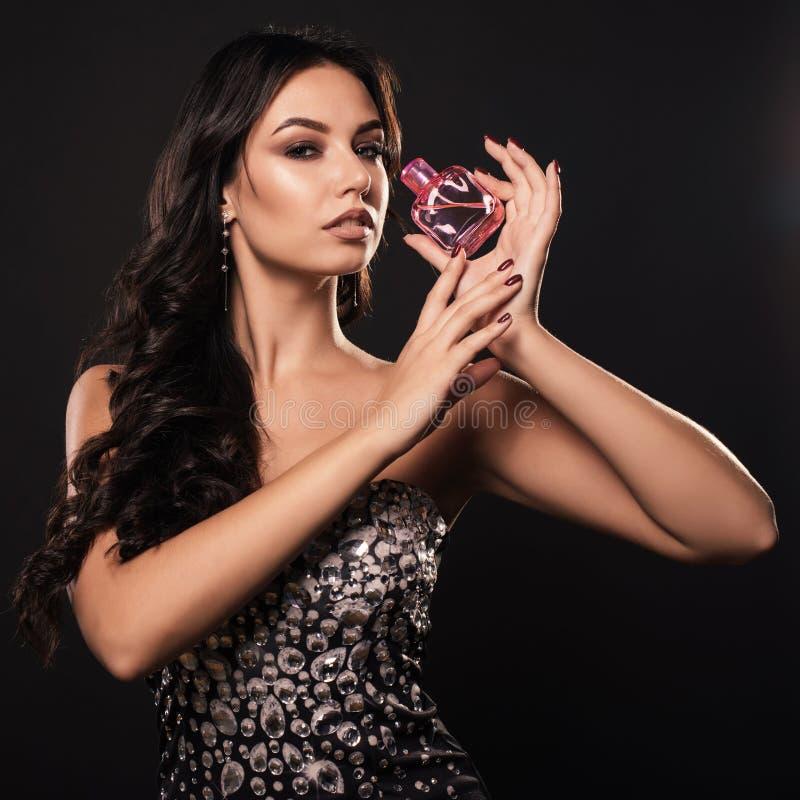 Elegante glamourvrouw in een mooie kleding met parfum op donkere achtergrond royalty-vrije stock foto