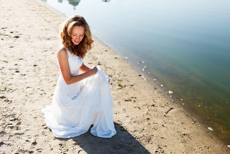 Elegante glimlachende meisjesbruid in een witte kleding op een zandig rivierstrand royalty-vrije stock foto's