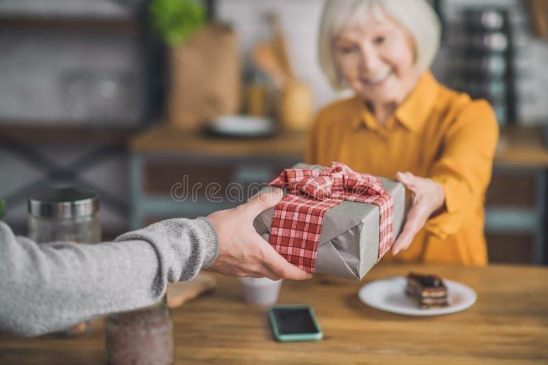 Elegante, gut aussehende, grauhaarige Frau mit Geschenkbox, die erfreut aussieht stockbilder