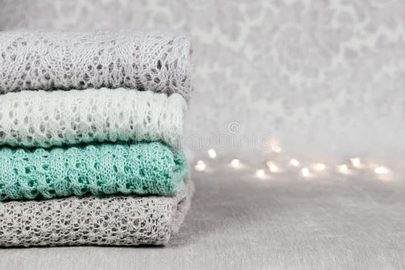 Elegante hizo punto los suéteres coloreados en colores pastel doblados en pila en fondo aterciopelado de la tela Géneros de punto fotos de archivo libres de regalías