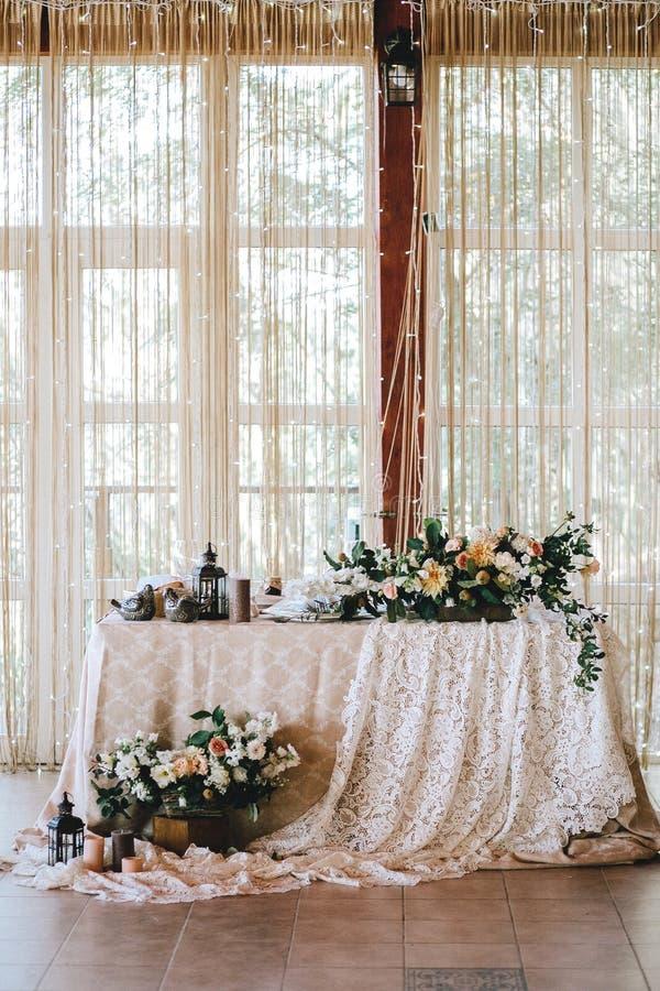 Elegante Hochzeitstafel im Stil der Weinlese und rustikales verziert mit Blumen, weißer Spitze, Tischdecke und Kerzen lizenzfreie stockfotografie