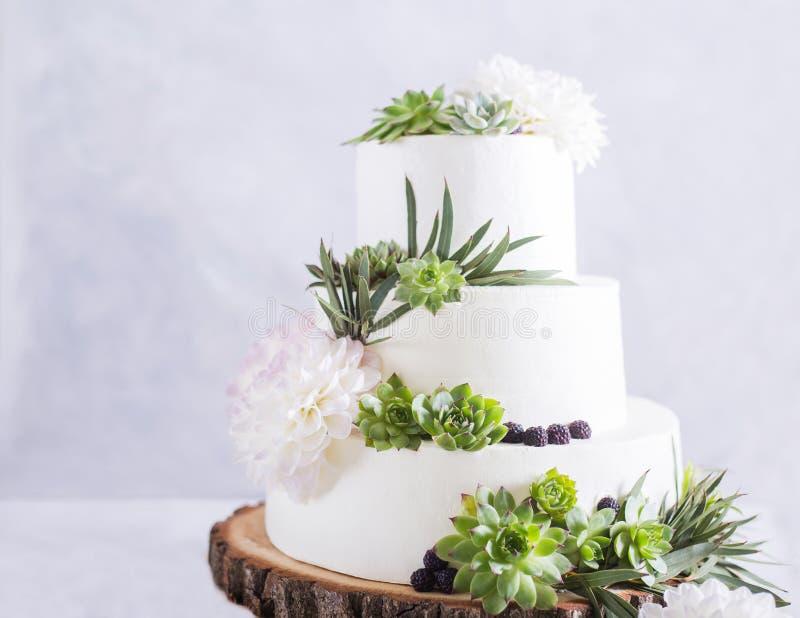 Elegante Hochzeitstorte mit Blumen und Succulents stockfoto
