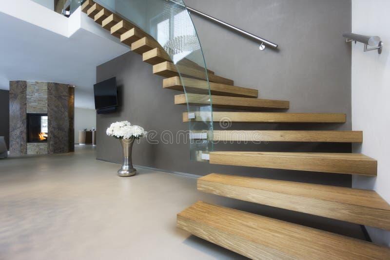 Elegante hout en glastrap in luxehuis stock afbeeldingen