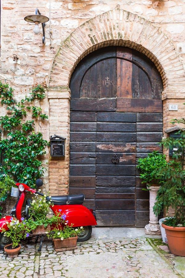 Elegante houten deur met rode vespa royalty-vrije stock afbeeldingen