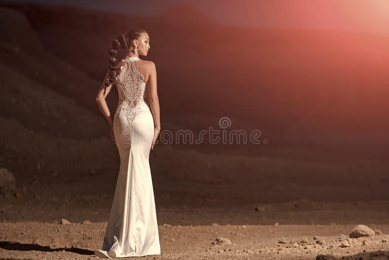 Elegante huwelijkskleding Vrouw in witte huwelijkskleding in woestijn stock foto
