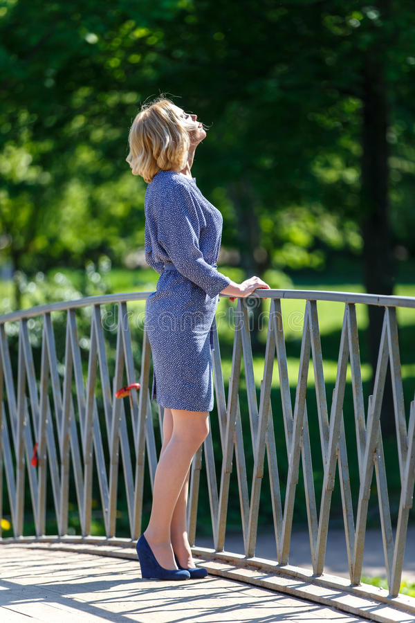 Elegante jonge blonde dame die de zon op de brug bekijken royalty-vrije stock afbeelding