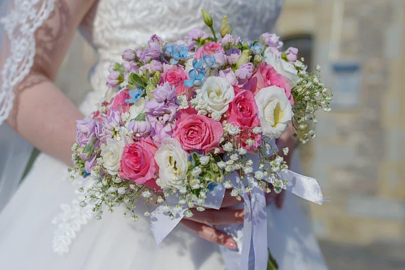 Elegante jonge bruid bij de huwelijksceremonie met nadruk op de hand die een bloemenregeling houden stock foto