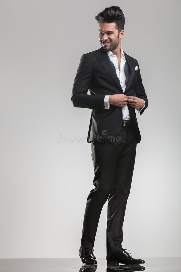 Elegante jonge mens die zijn smoking sluiten royalty-vrije stock foto