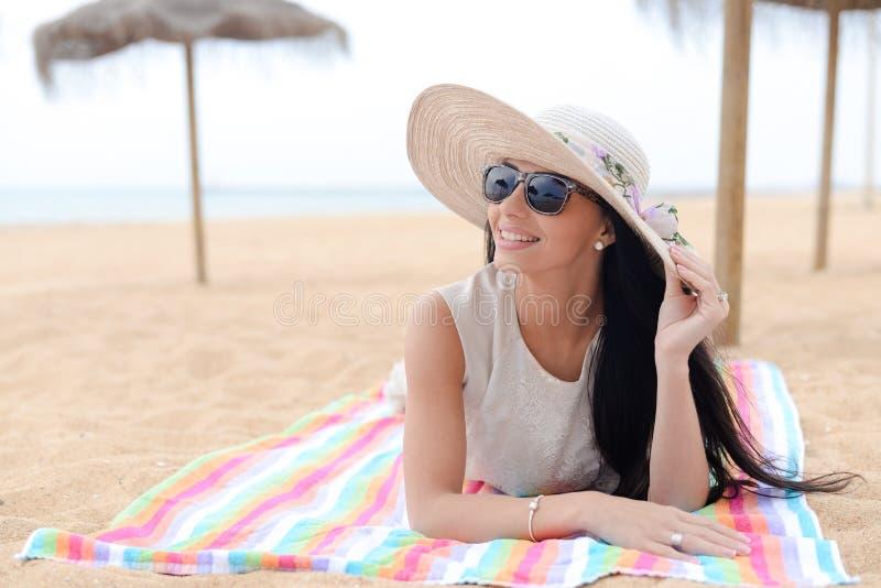 Elegante jonge mooie dame die op zandig strand liggen Het concept van de vakantie stock foto