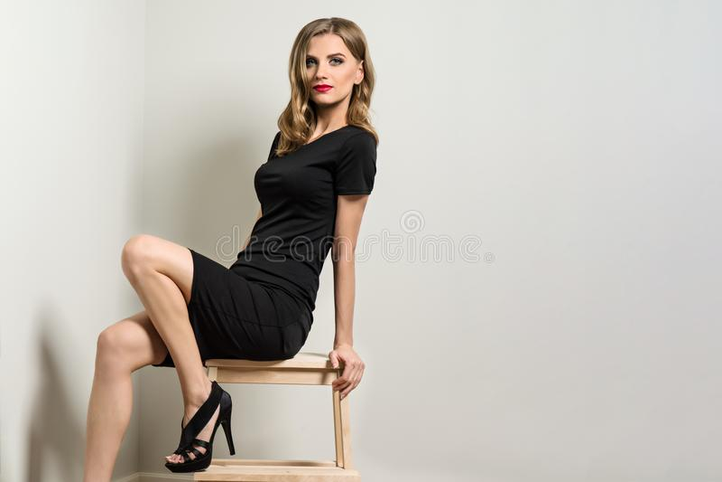 Elegante jonge vrouw blond in zwarte kleding royalty-vrije stock afbeeldingen