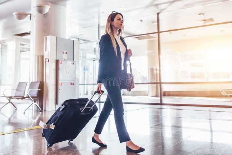 Elegante jonge vrouw die en haar koffer in de luchthaventerminal lopen trekken stock afbeelding