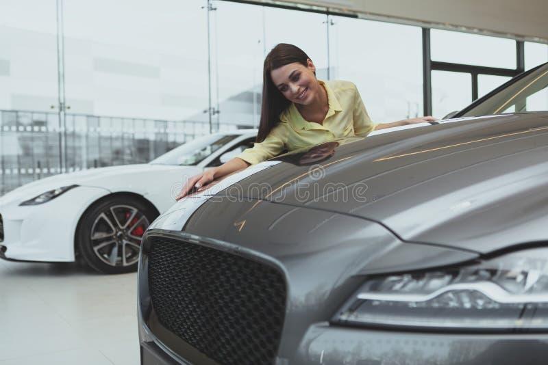Elegante jonge vrouw die nieuwe auto kopen bij het handel drijven royalty-vrije stock foto