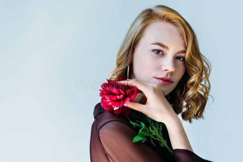 elegante jonge vrouw die rode bloem houden en camera bekijken royalty-vrije stock afbeelding