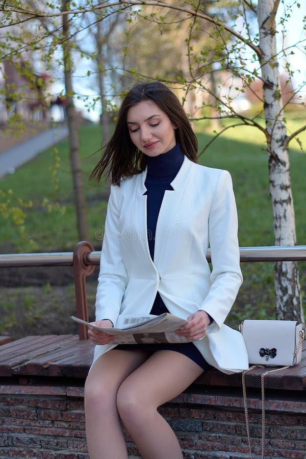 Elegante jonge vrouw op een stadsstraat met een krant in haar handen stock afbeelding