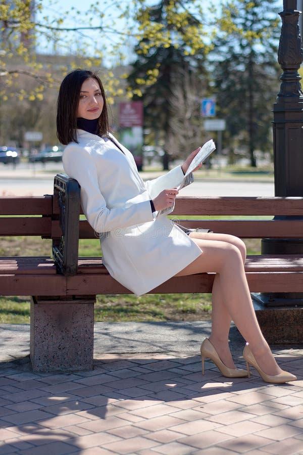 Elegante jonge vrouw op een stadsstraat met een krant in haar handen stock foto