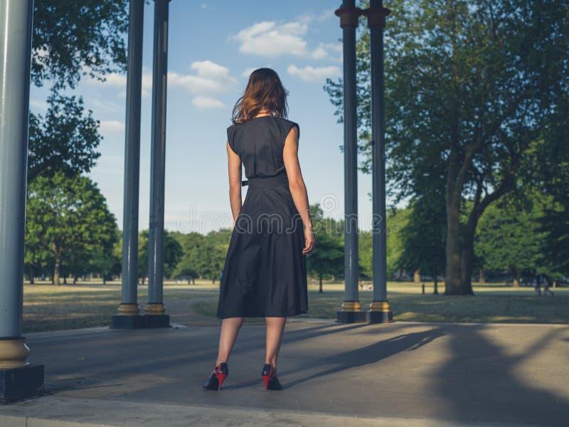 Elegante jonge vrouw in park bij zonsondergang royalty-vrije stock foto's