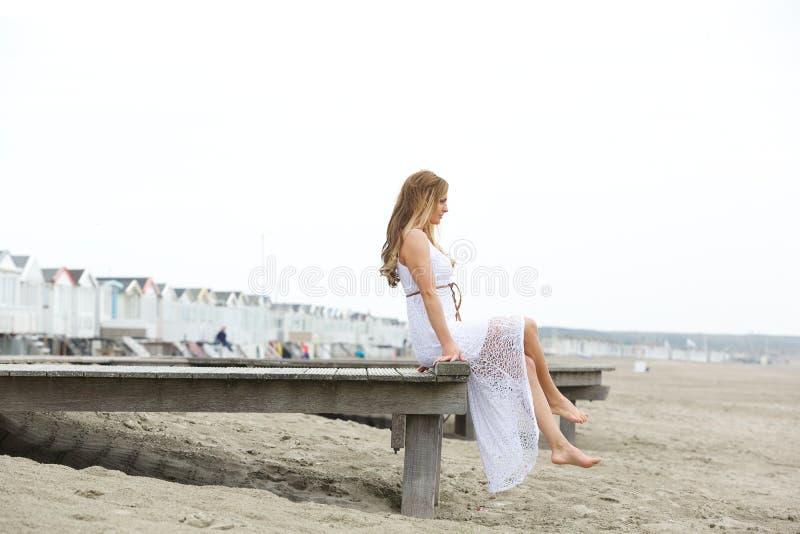 Elegante jonge vrouwenzitting door de kust royalty-vrije stock foto's