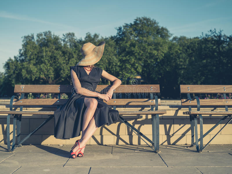 Elegante jonge vrouwenzitting op parkbank stock foto's