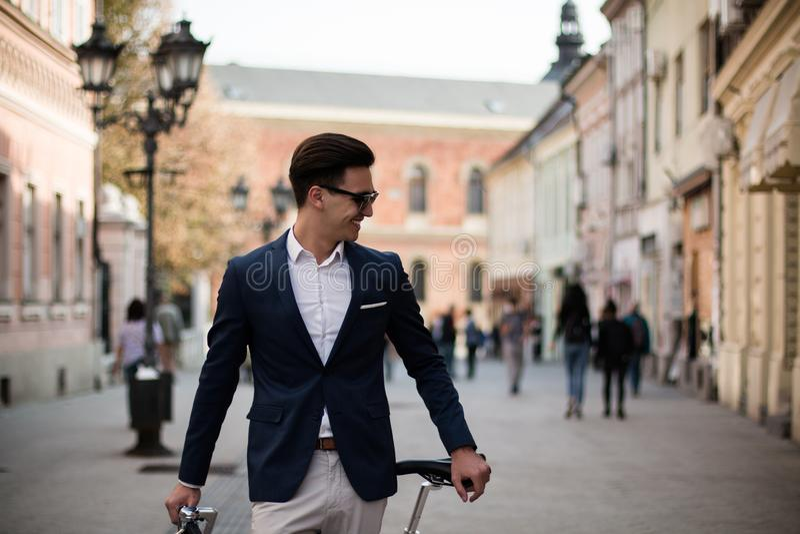 Elegante jonge zakenman met fiets in openlucht stock foto's
