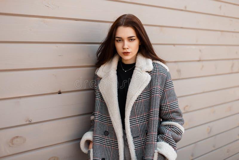 Elegante junge brunette Frau in den grauen Hosen der Weinlese in einem schwarzen Hemd in einer modernen karierten Jacke steht Ste stockfotos