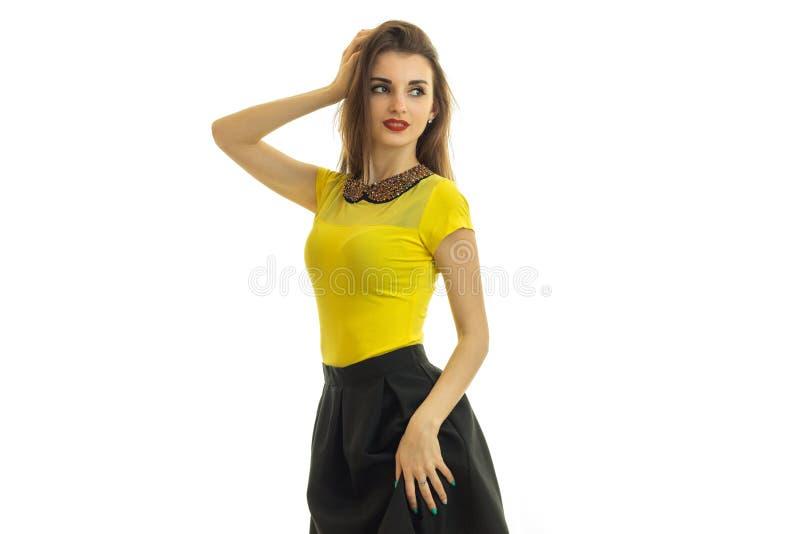 Elegante junge Brunettefrau mit den roten Lippen im Gelb mit schwarzem Anzug stockbild