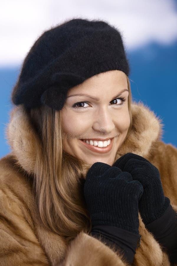 Elegante junge Frau, die das Winterlächeln genießt stockfoto