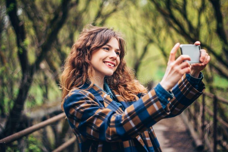 Elegante junge Frau, die intelligentes Telefon im Park lächelt und verwendet lizenzfreies stockbild