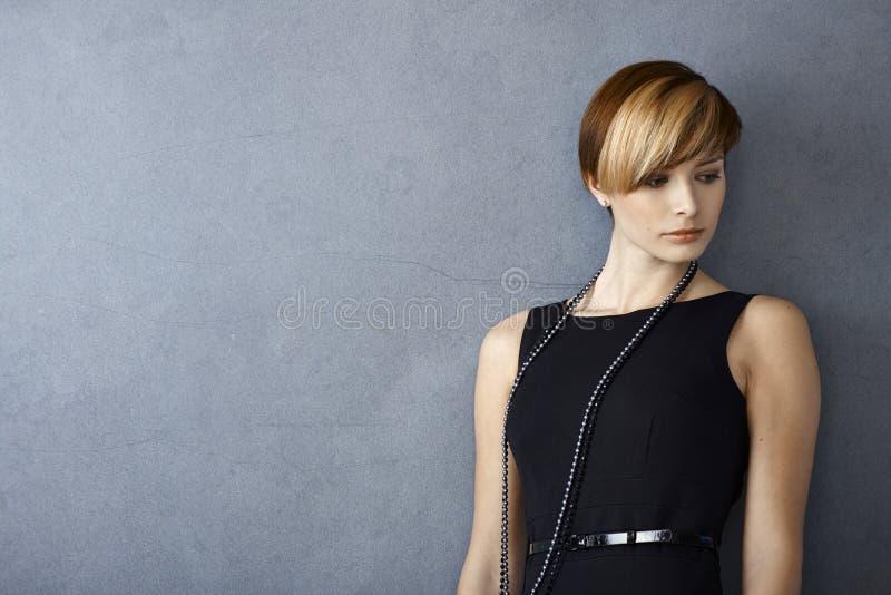 Elegante junge Frau im schwarzen Kleid lizenzfreie stockbilder