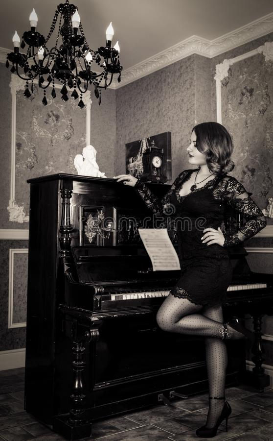 Elegante junge Frau im schwarzen Kleid, das nahe dem Klavier aufwirft lizenzfreie stockfotografie