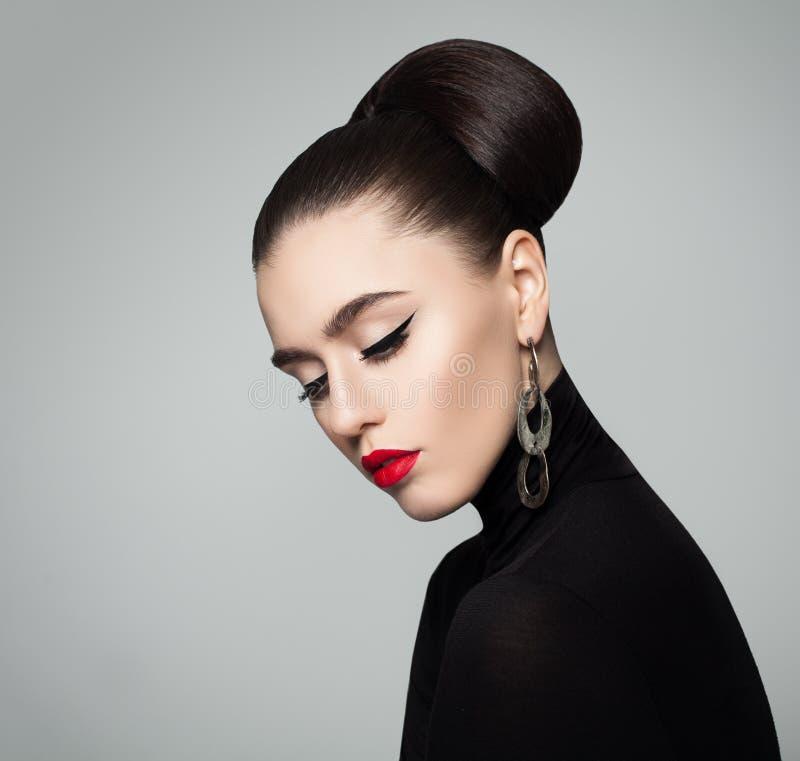 Elegante junge Frau mit Haar-Brötchen-Frisur stockfoto