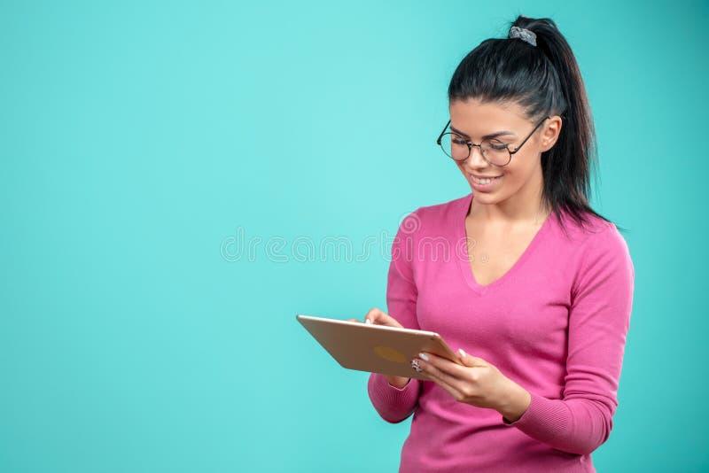 Elegante junge Geschäftsfrau, die mit der Tablette lokalisiert auf dem blauen Hintergrund arbeitet lizenzfreies stockbild