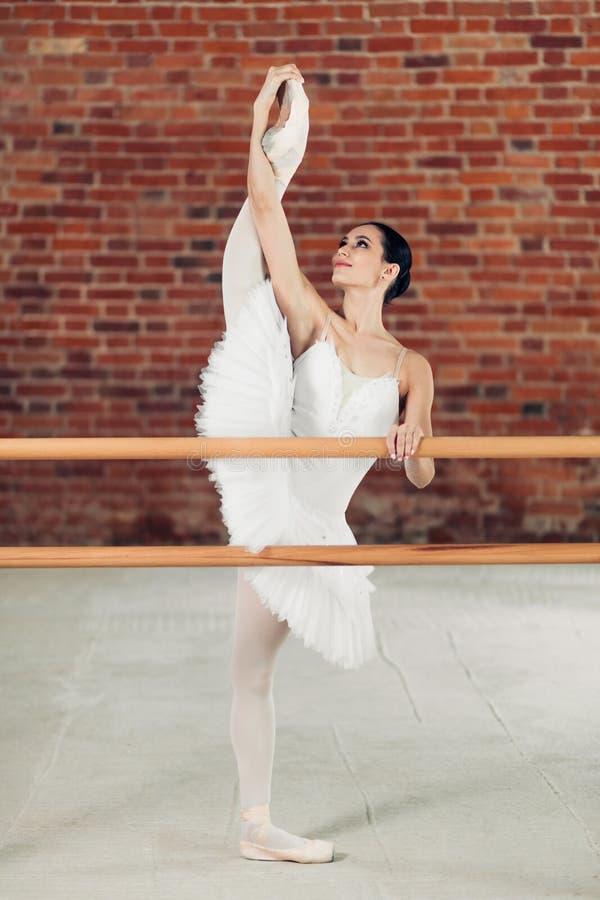 Elegante junge lächelnde Frau im Ballettröckchen, das Beine in der Tanzklasse ausdehnt lizenzfreie stockfotos