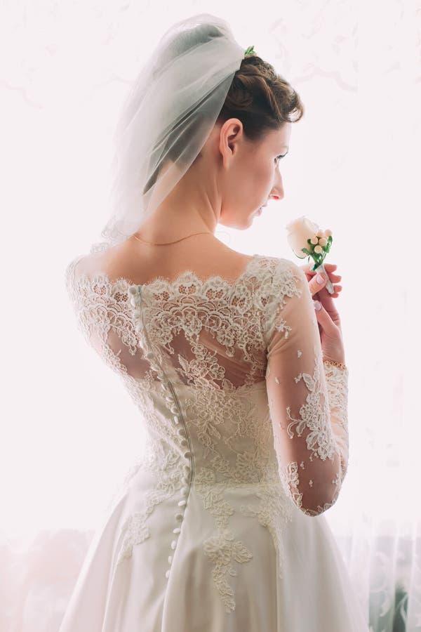 Elegante junge und träumerische schöne Braut in einem luxuriösen Spitzehochzeitskleid, das Rosarose hält lizenzfreies stockfoto