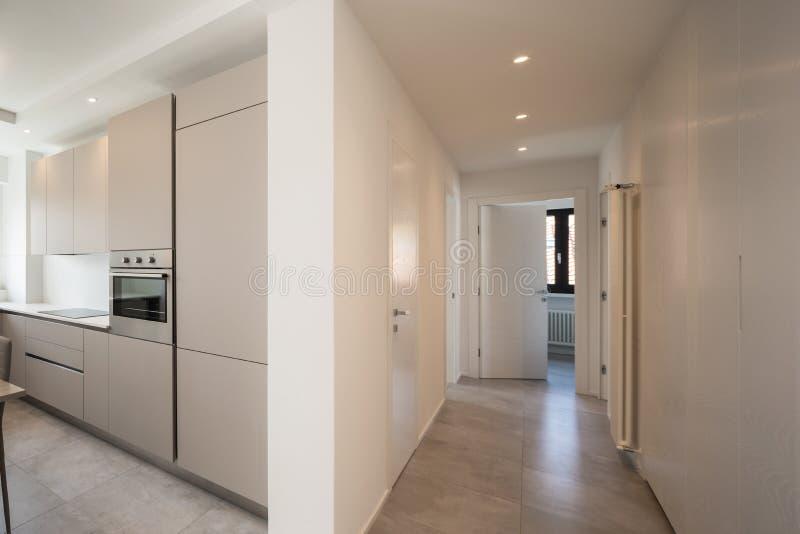 Elegante Küche und Korridor mit Scheinwerfern in der modernen Wohnung lizenzfreies stockfoto