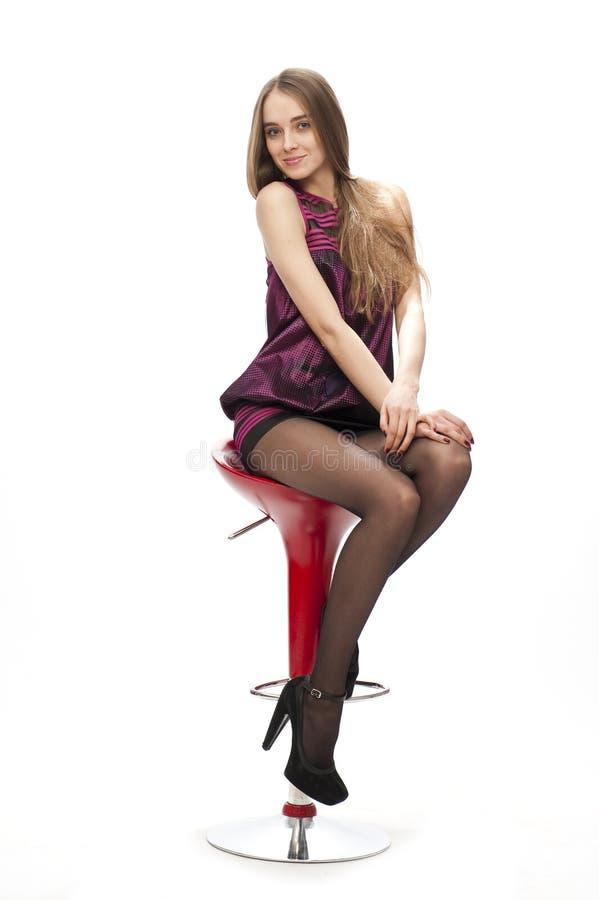 Elegante kaukasische lächelnde Frau auf dem Stabstuhl stockbild