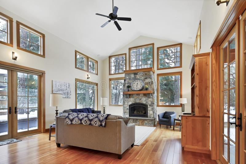 Elegante leefruimte met hoge gewelfde plafond en steenopen haard stock foto