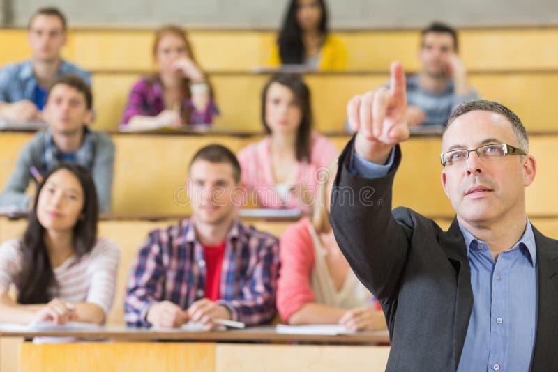 Elegante leraar en studenten bij de zaal van de universiteitslezing royalty-vrije stock fotografie