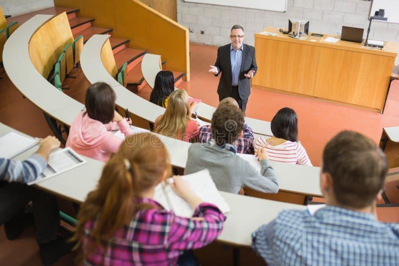 Elegante leraar met studenten bij de lezingszaal royalty-vrije stock afbeelding