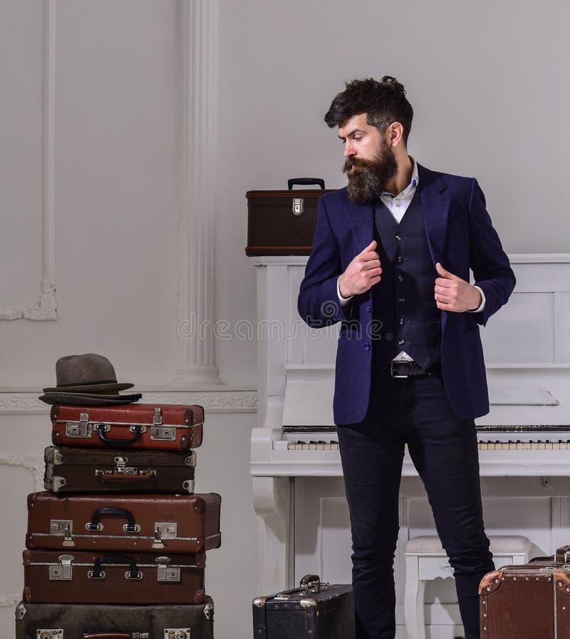 Elegante machista en la cara pensativa que coloca la pila cercana de maleta del vintage Hombre, viajero con la barba y bigote con fotos de archivo libres de regalías