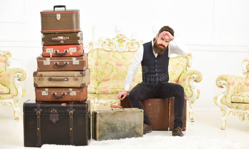 Elegante macho na cara restrita senta a pilha próxima cansado da mala de viagem do vintage O homem, o mordomo com barba e o bigod imagens de stock