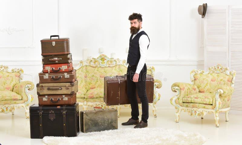 Elegante macho sul fronte rigoroso porta la valigia d'annata Bagagli e concetto di rilocazione Uomo, maggiordomo con la barba e fotografie stock