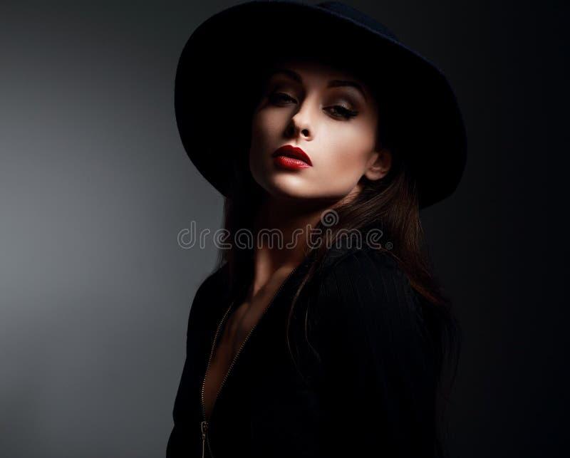 Elegante Make-upfrau in fashon Hut und in roten Lippen, die auf dunklem s aufwerfen stockbilder